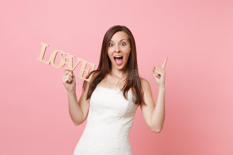Портрет изумленной женщины невесты в платье свадьбы указывая указательный палец вверх по удержанию деревянных писем слова любит д стоковые фотографии rf