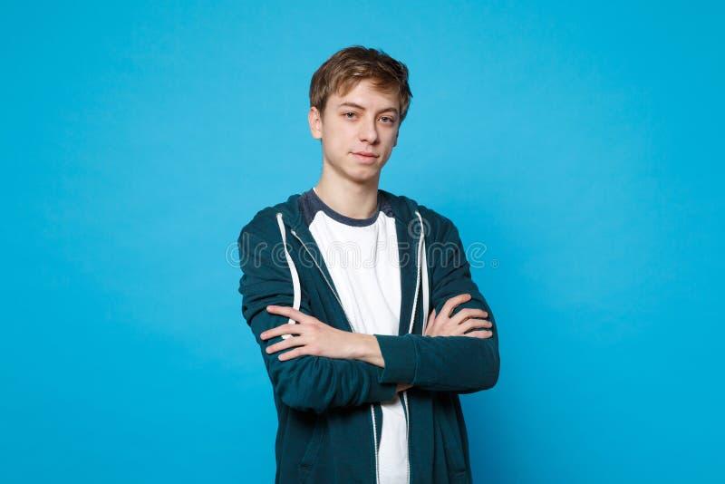 Портрет красивого молодого человека в случайных одеждах стоя смотрящ в сторону держащ руки сложил изолированный на голубой стене стоковое изображение rf
