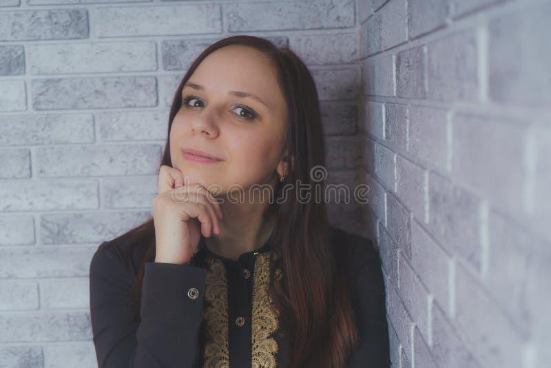 Портрет красивого положения счастья молодой женщины на серой предпосылке кирпича стены grunge текстуры цемента стоковое фото
