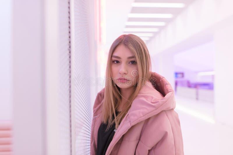 Портрет красивой белокурой девушки в светлом - розовая предпосылка Красивая девушка представляя в розовом интерьере стоковые фотографии rf