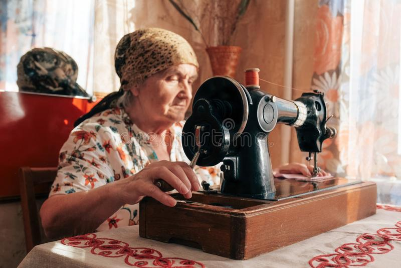 Портрет крупного плана старухи используя швейную машину, 70 лет белошвейки работая дома стоковое фото