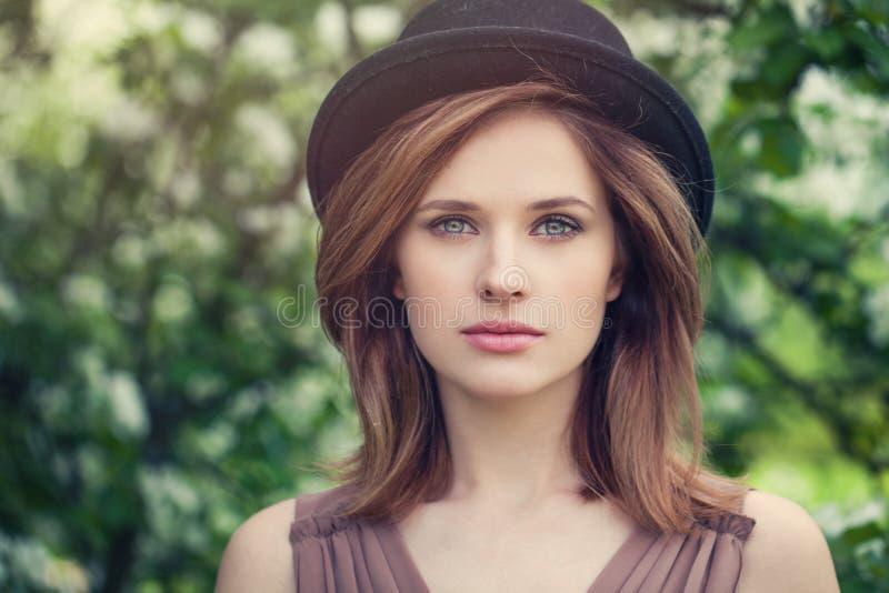 Портрет крупного плана стороны женщины на открытом воздухе Милая девушка в шляпе на предпосылке листвы растительности стоковые изображения