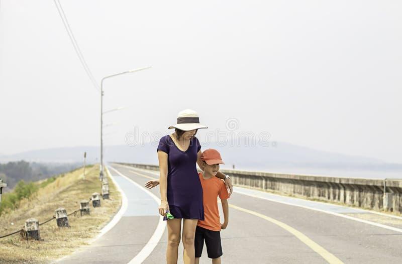 Портрет матери и сына идя на горы и воду предпосылки улицы на запруде Krasiew, Supanburi Таиланде стоковые изображения