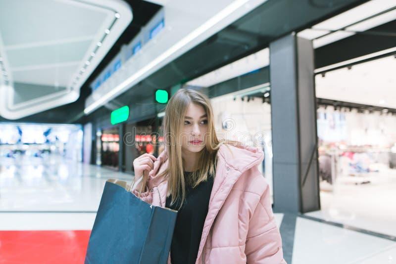 Портрет милой девушки с покупками в руках современного, красивого торгового центра женщина ног принципиальной схемы мешка предпос стоковое фото