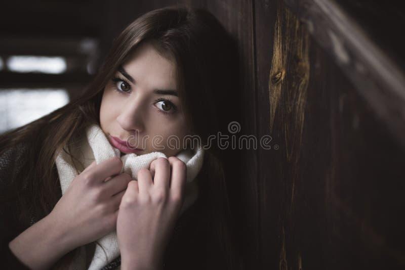 Портрет милой девушки с руками близко к ее стороне на шарфе Холодный сезон зимы Интерьер получившихся отказ дома или сарая от тем стоковое изображение rf