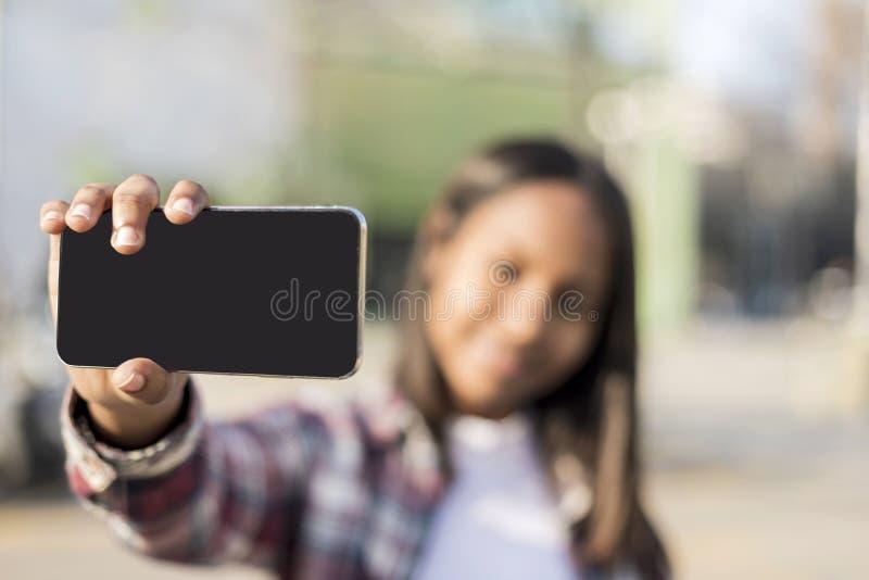Портрет молодого Афро-американского outdoors положения женщины пока принимающ selfie в солнечном дне стоковые фото