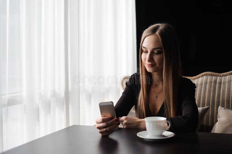 Портрет молодого мобильного телефона пользы коммерсантки пока сидящ в удобной кофейне во время пролома работы стоковые фотографии rf