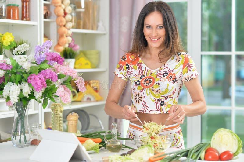 Портрет молодой женщины подготавливая очень вкусную здоровую еду в кухне стоковые фото