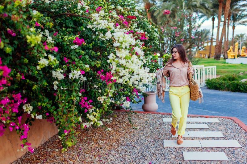 Портрет молодой стильной женщины идя тропическими цветками в Египте каникула территории лета katya krasnodar стоковые изображения rf