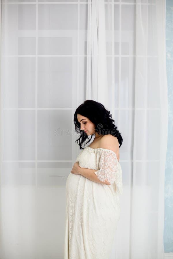 Портрет моды счастливой беременной женщины в белом платье стоковые фото