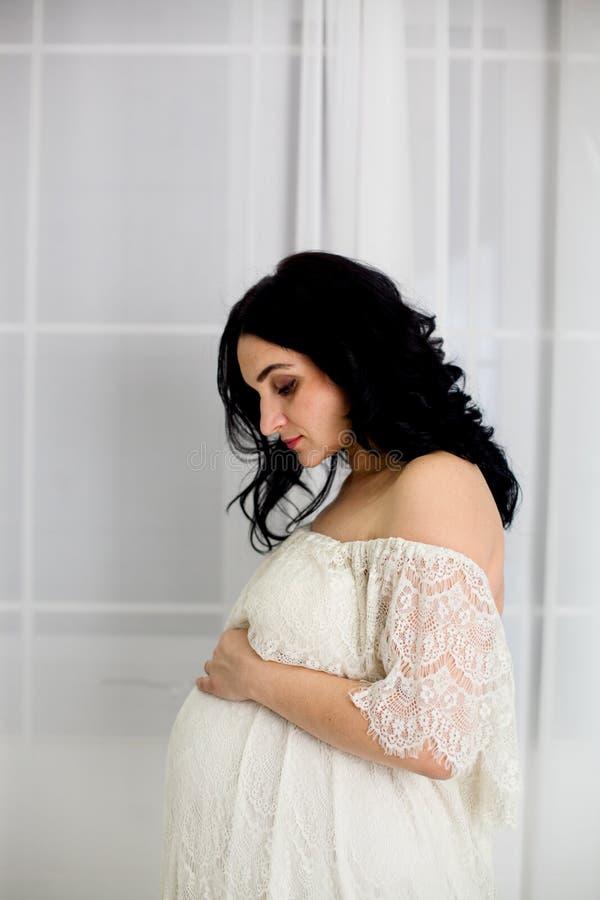 Портрет моды счастливой беременной женщины в белом платье стоковая фотография rf