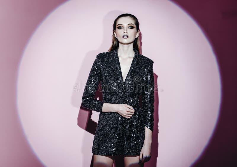 Портрет моды ультрамодной девушки с волосами вытянул назад и стильный макияж в сияющем дежурном g платья рядом со стеной стоковые изображения rf