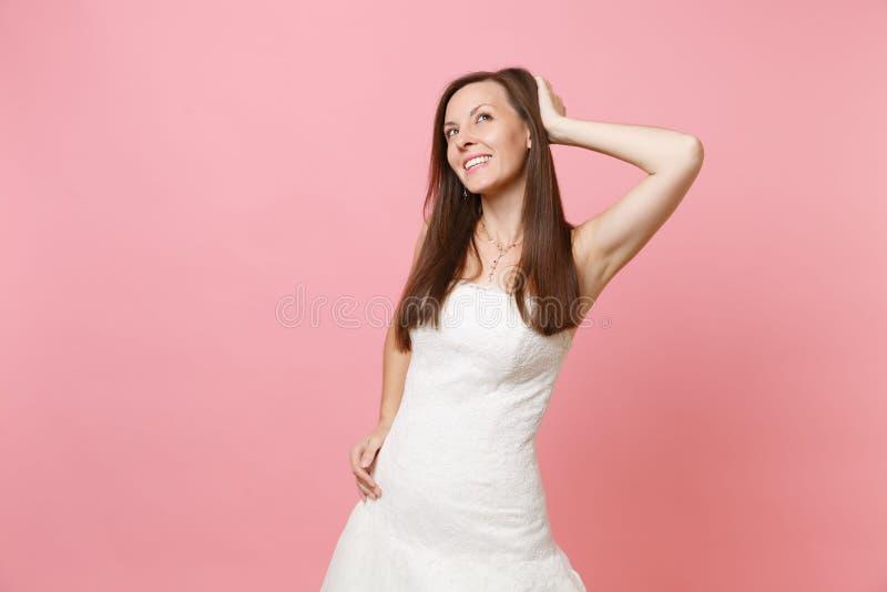 Портрет нежной женщины невесты в белом платье свадьбы стоя мечтающ смотреть вверх по держать руку около головы изолированной даль стоковое изображение