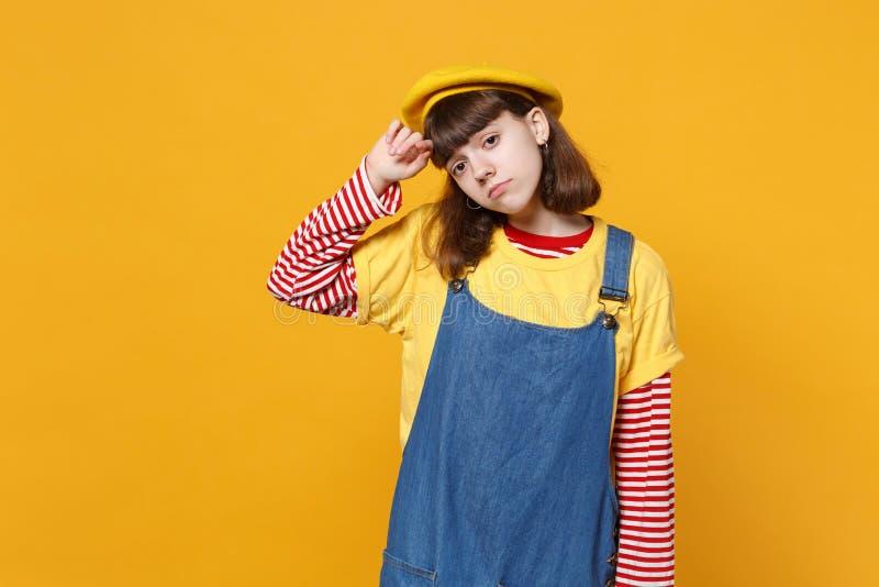 Портрет неудовлетворенного грустного подростка девушки во французском берете, sundress джинсовой ткани смотря в сторону изолирова стоковое фото