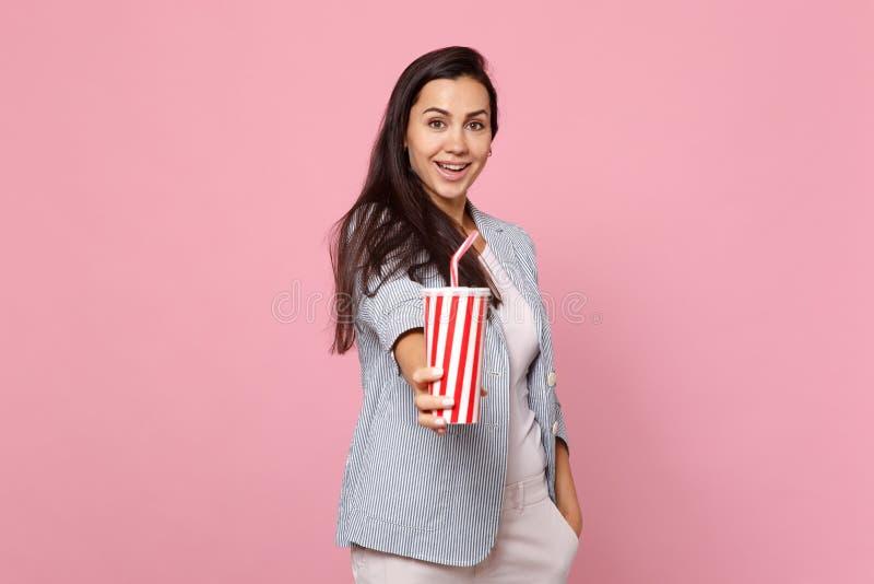 Портрет привлекательной жизнерадостной молодой женщины в чашке striped владением куртки пластиковой колы или соды изолированных н стоковое изображение rf