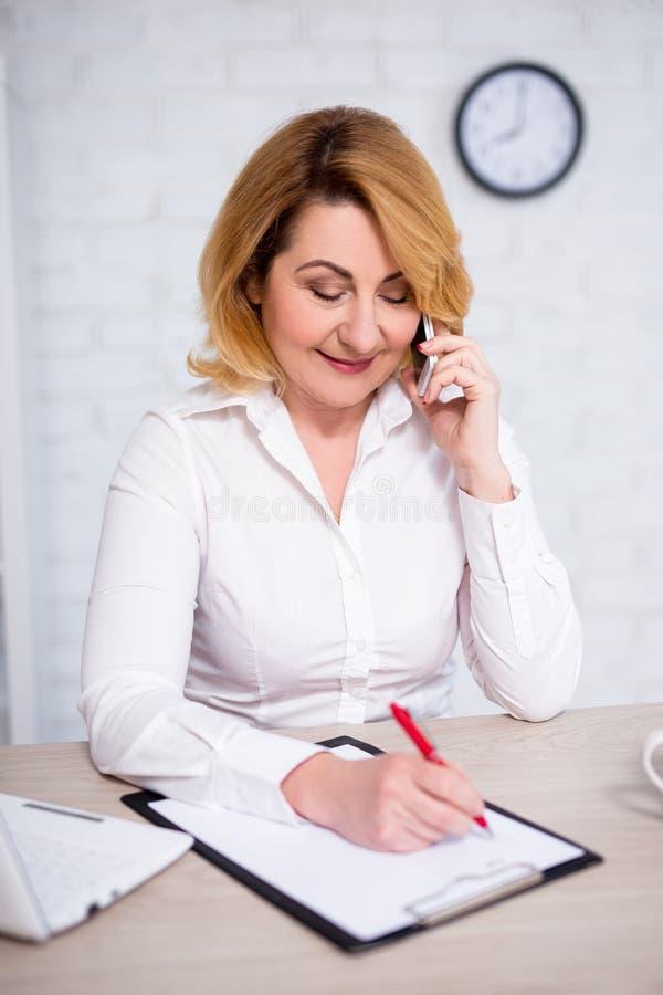 Портрет привлекательной зрелой бизнес-леди сидя в офисе, говоря по телефону и писать что-то на доске сзажимом для бумаги стоковые фото