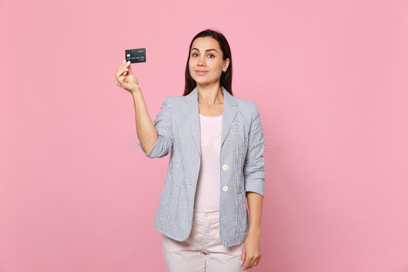 Портрет привлекательной милой молодой женщины в striped карте кредитного банка удерживания куртки изолированной на розовой пастел стоковая фотография rf