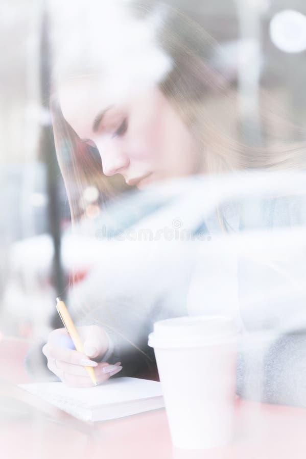 Портрет привлекательной молодой девушки журналиста с ручкой и блокнота в кафе за витриной взгляд Не-контраста стоковые изображения rf
