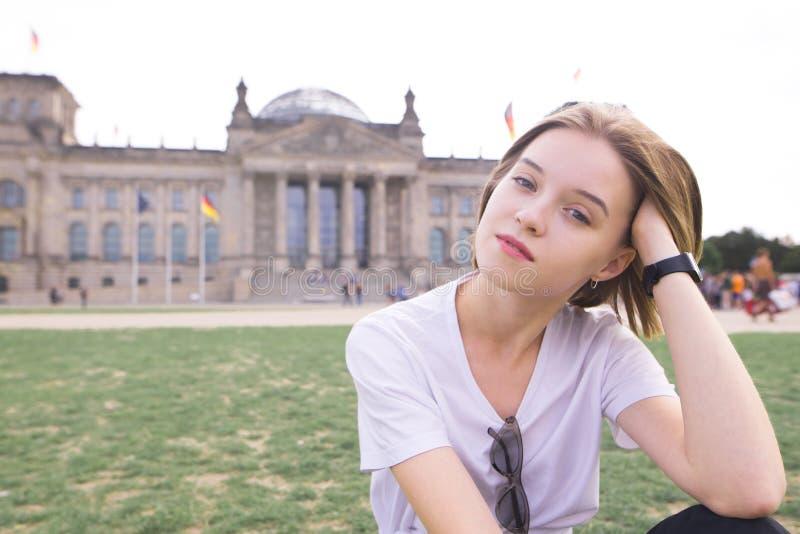Портрет привлекательной девушки сидя на лужайке на предпосылке Reystag, смотря в камеру и усмехаться стоковые фото
