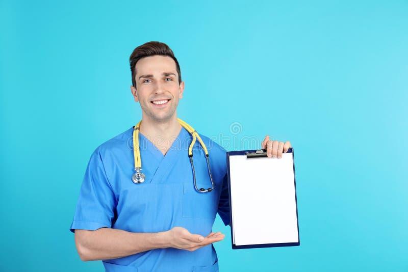 Портрет помощника врача со стетоскопом и доской сзажимом для бумаги на предпосылке цвета стоковые фотографии rf