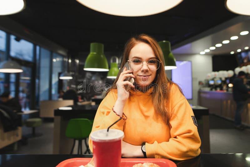 Портрет девушки студента в кафе, звенящ по телефону, смотрящ в камеру и усмехаться стоковое изображение rf