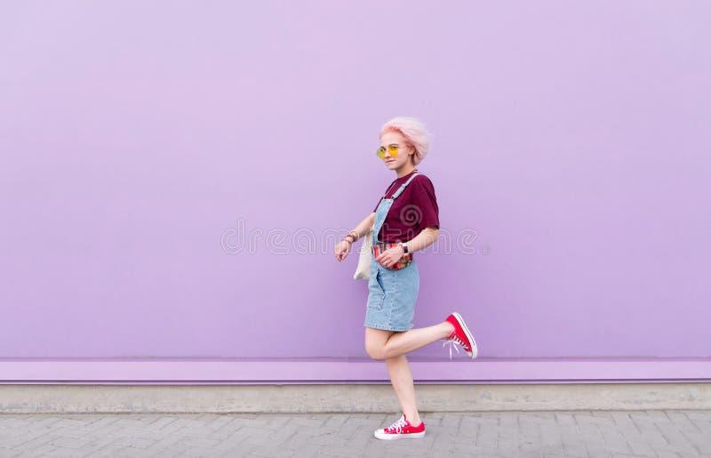 Портрет девушки с интересным взглядом на пурпурной предпосылке стоковое изображение