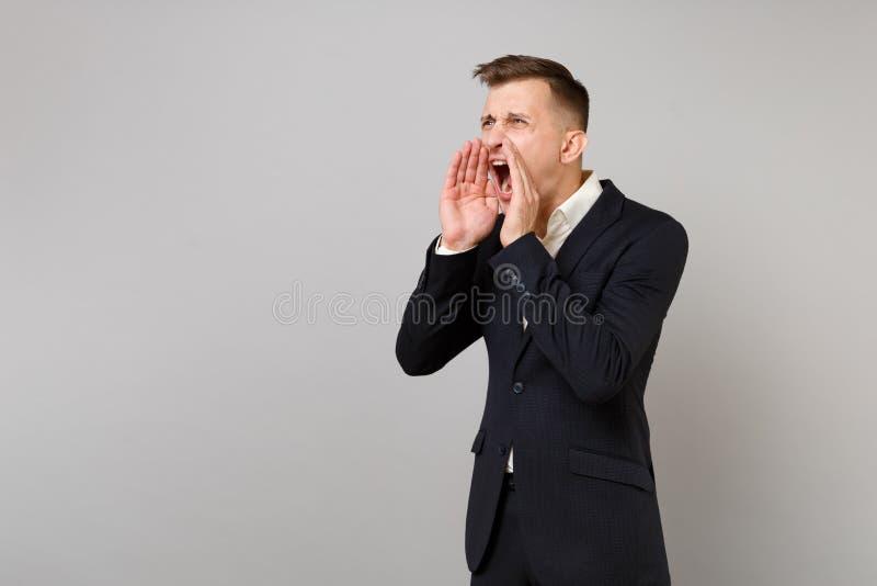 Портрет сердитого молодого бизнесмена в классической черной рубашке костюма кричащей с жестом рукой изолированного на серой стене стоковые фото