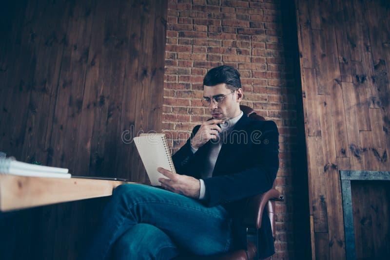 Портрет славного красивого стильного ультрамодного умного чтения основателя компании парня замечает расписание недели дневника пл стоковое фото