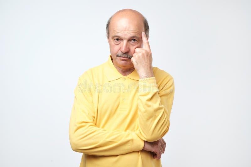 Портрет случайного зрелого человека в желтой рубашке думая и смотря озадаченный стоковая фотография
