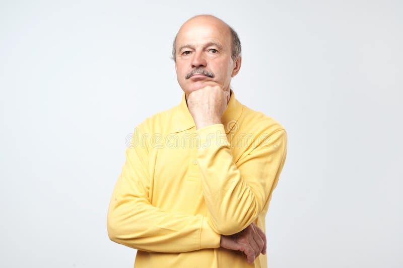Портрет случайного зрелого человека в желтой рубашке думая и смотря озадаченный стоковые изображения