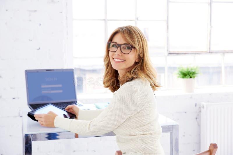 Портрет смеяться зрелой коммерсанткой сидя на столе офиса и используя ее цифровой планшет стоковые изображения