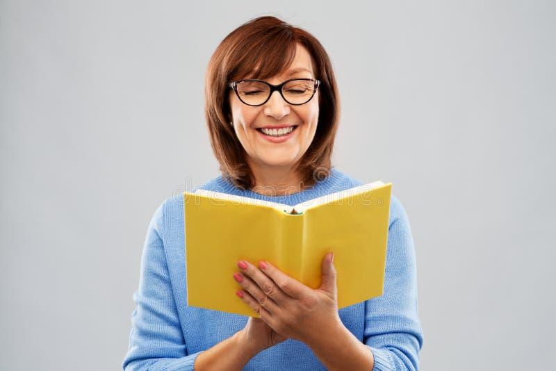 Портрет старшей женщины в книге чтения стекел стоковые изображения rf