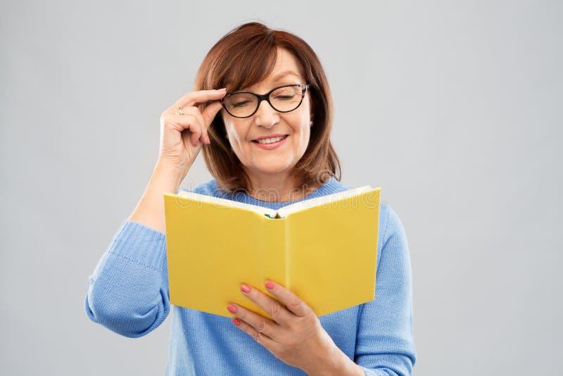 Портрет старшей женщины в книге чтения стекел стоковое изображение