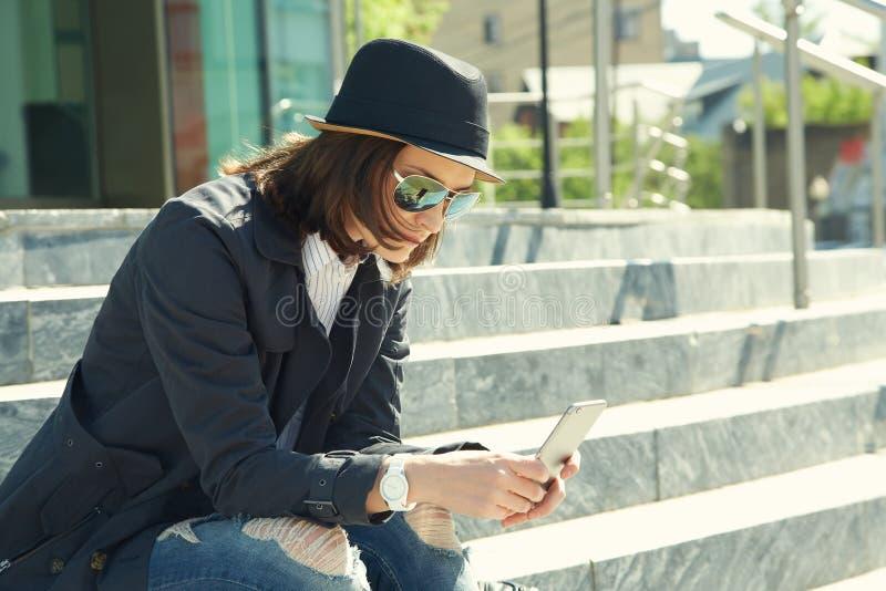 Портрет стильной женщины в шляпе и солнечных очках со смартфоном стоковые изображения rf