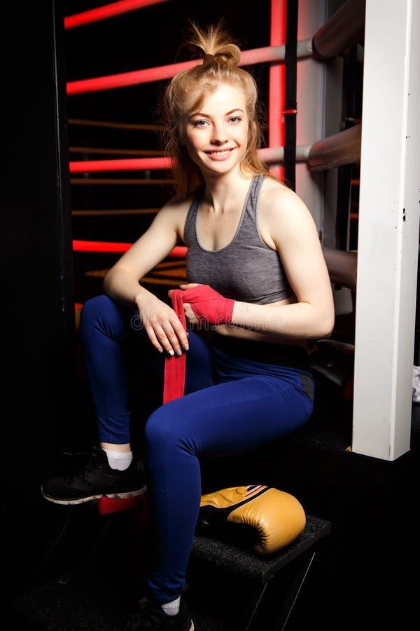 Портрет счастливого женского боксера создавая программу-оболочку красные повязки сидя кольцом боя стоковое фото
