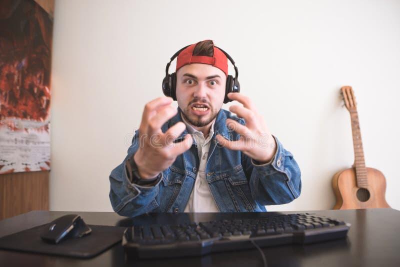 Портрет эмоционального gamer с наушниками и борода за видеоиграми игры дома стоковые фото