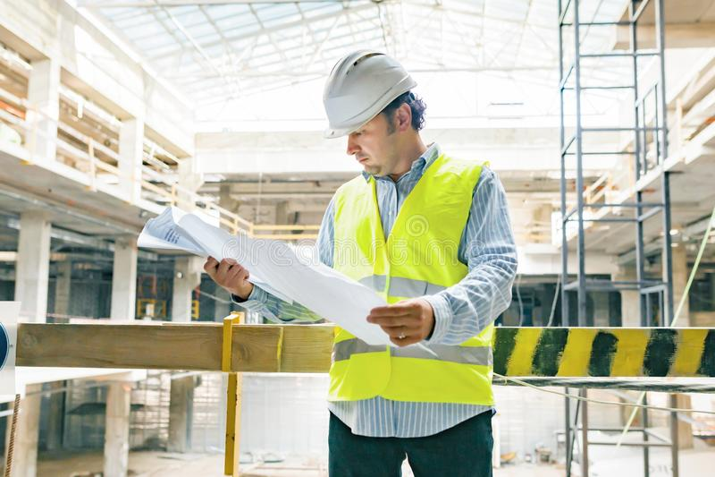 Портрет уверенного мужского построителя, менеджера, инженера со строя планом на строительной площадке r стоковое фото rf