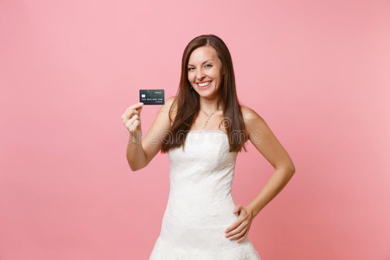 Портрет усмехаясь женщины невесты в платье свадьбы красивого шнурка белом держа кредитную карточку на розовой пастели стоковое фото