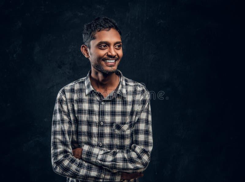 Портрет усмехаясь индийского парня нося checkered рубашку представляя с его пересеченными оружиями и выглядя косой стоковые изображения
