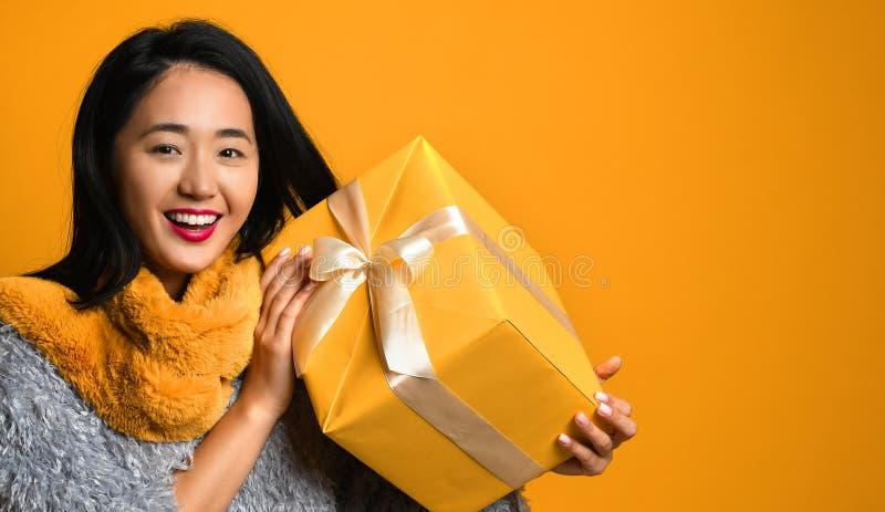 Портрет усмехаясь милой подарочной коробки удерживания девушки изолированной над желтой предпосылкой стоковые изображения rf