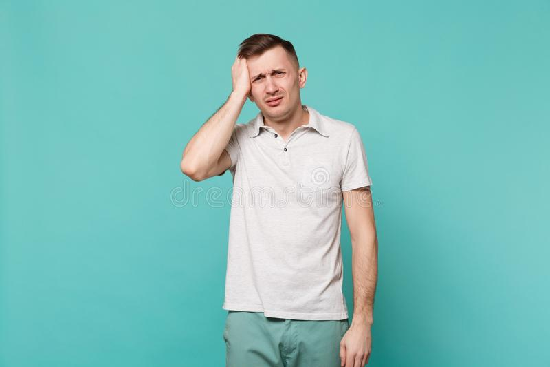 Портрет уставшего неудовлетворенного молодого человека в случайных одеждах стоя кладущ руку на голову изолированную на голубой би стоковое фото rf