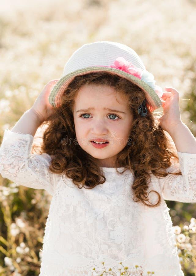 Портрет расстроенной маленькой девочки в соломенной шляпе с вьющиеся волосы стоковая фотография