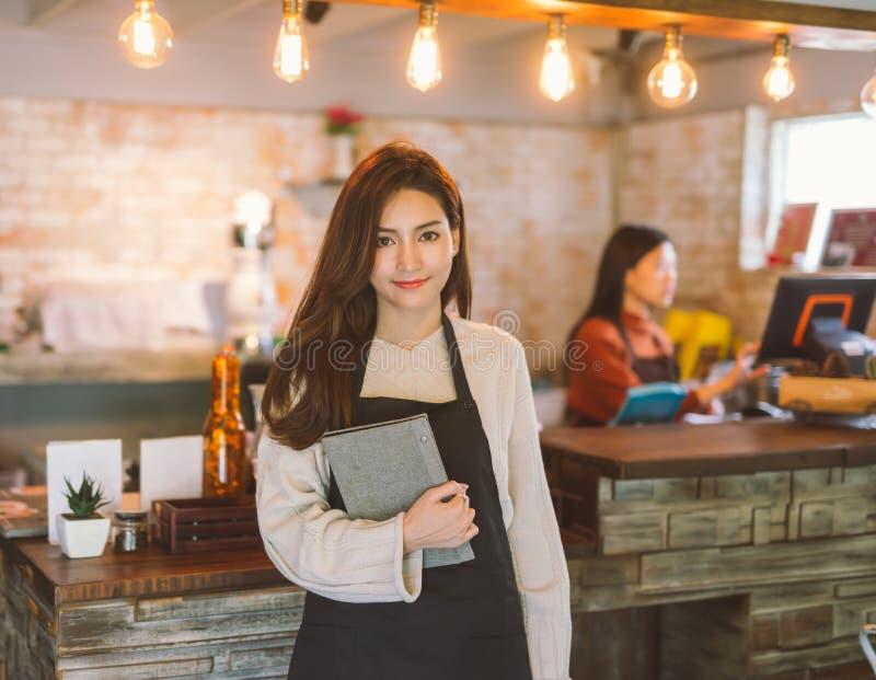 Портрет рисбермы и стоять азиатского меню удерживания официантки девушки нося в кофе shop0 стоковые изображения rf