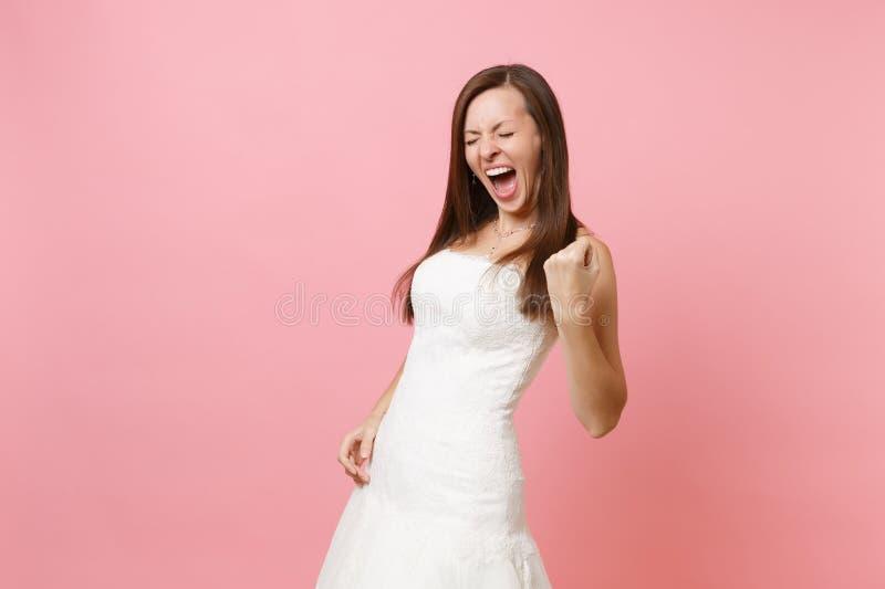 Портрет осчастливленной женщины невесты в белом положении платья свадьбы делая кулак жеста победителя обхватывая изолированный на стоковые фотографии rf