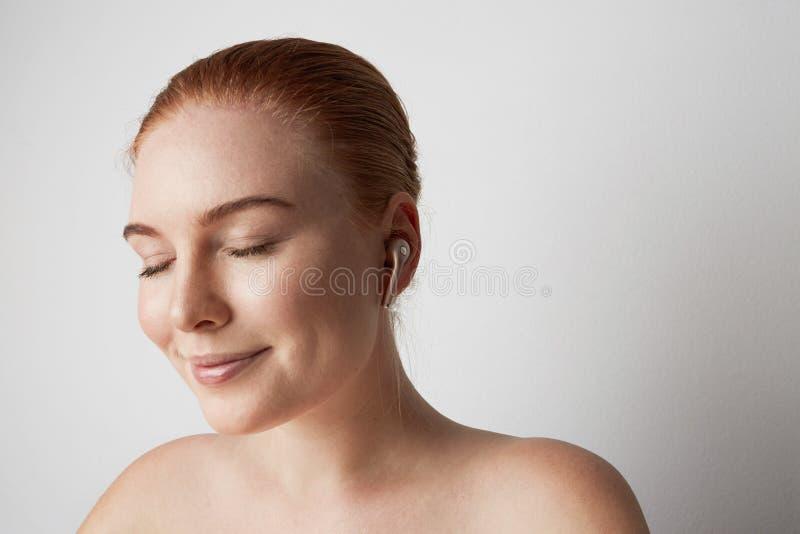 Портрет очаровывая женщины redhead с романтичной улыбкой и музыкой закрытых глаз слушая с беспроводным наушником в ухе стоковые изображения
