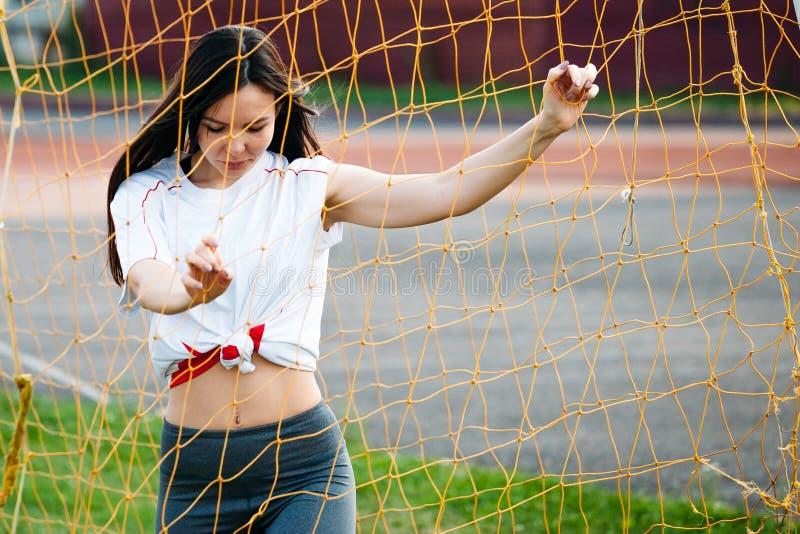 Портрет sporty женщины с длинными волосами около цели футбола стоковая фотография