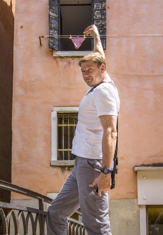 Ðœan traînant la lingerie pour sécher sur une rue italienne, l'effet de la tromperie/d'illusion, Venise, Italie images libres de droits