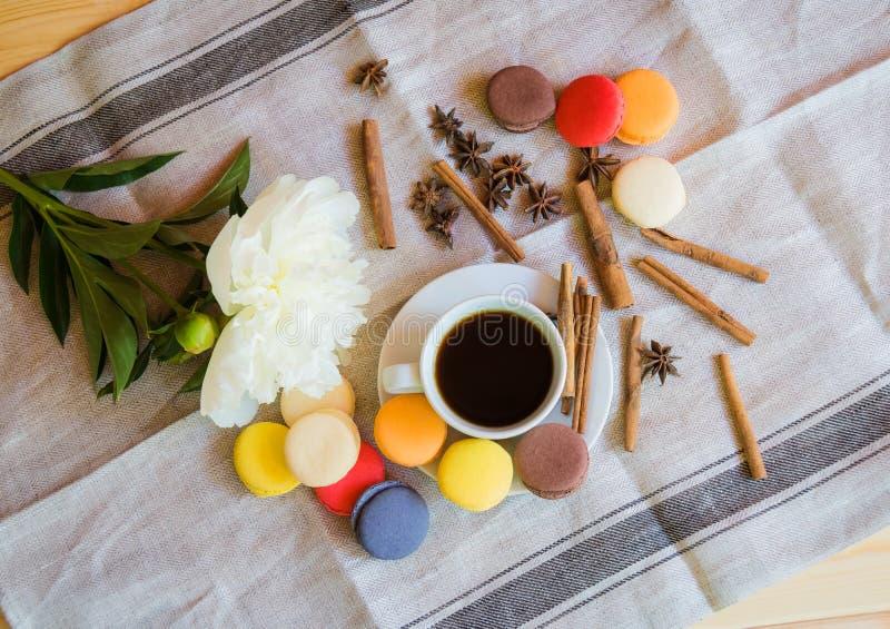 Ð ¡咖啡、白色牡丹花、五颜六色的蛋白杏仁饼干和香料 免版税图库摄影