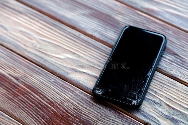 Ð ¡ loseup有说谎在木桌上的残破的屏幕玻璃的黑色智能手机 落下的电话,残破的小配件,电子的概念 免版税图库摄影