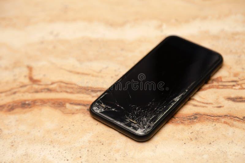 Ð ¡ loseup有说谎在木桌上的残破的屏幕玻璃的黑色智能手机 落下的电话,残破的小配件,电子的概念 免版税库存图片